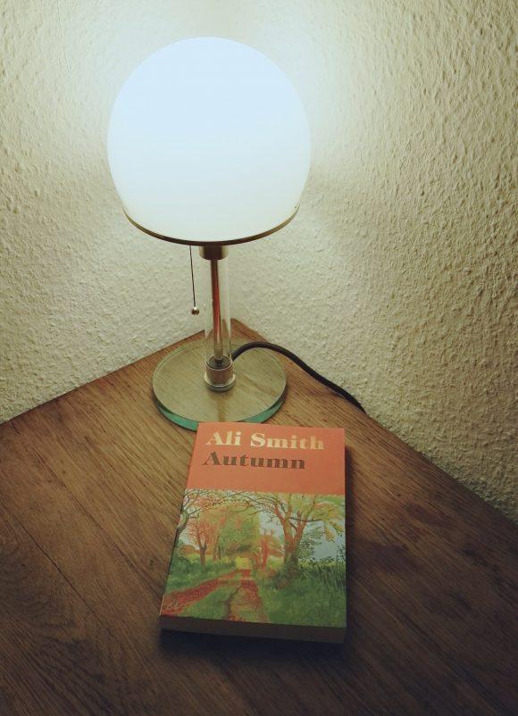 """Dieses Bild zeigt Ali Smith neuen Roman """"Autumn"""" auf einem Holztisch unter einer Lampe platziert."""