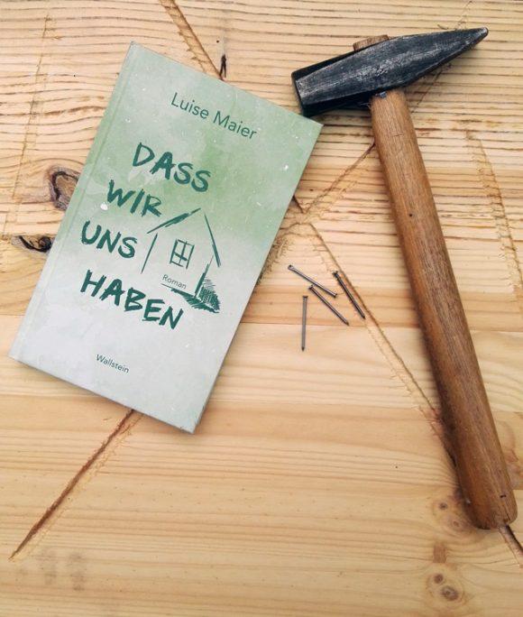 """Dieses Bild zeigt das Cover von Luise Maiers Debütroman """"Dass wir uns haben"""" auf einer Holzplatte mit Hammer und Nägeln."""