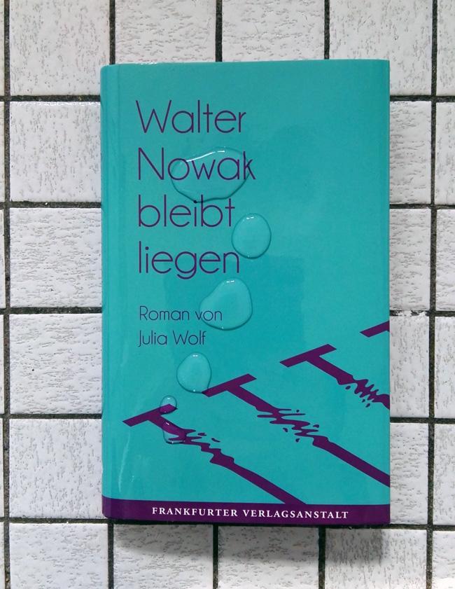 Dieses Bild zeigt das Cover von Julia Wolfs Debütroman Walter Nowak bleibt liegen vor einem Fließenhintergrund.